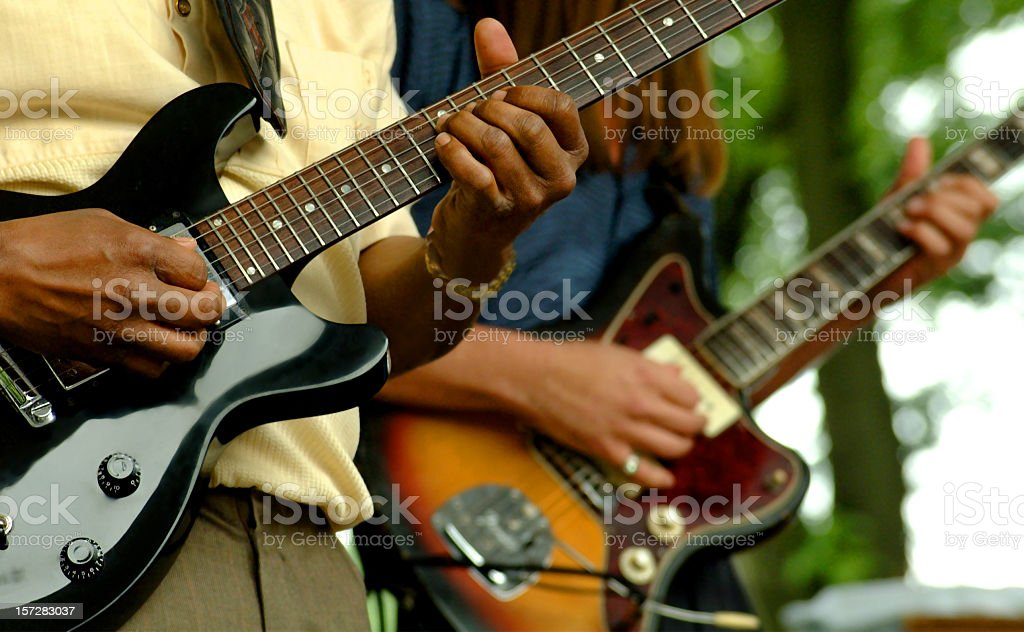 Close up of two people playing guitars stock photo