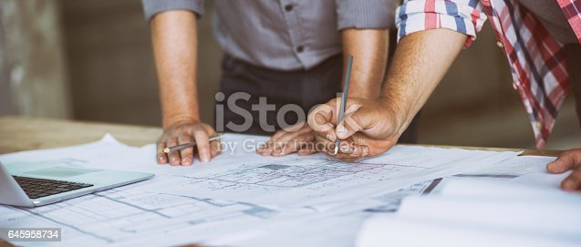 istock Close up of two people reviewing building blueprints 645958734