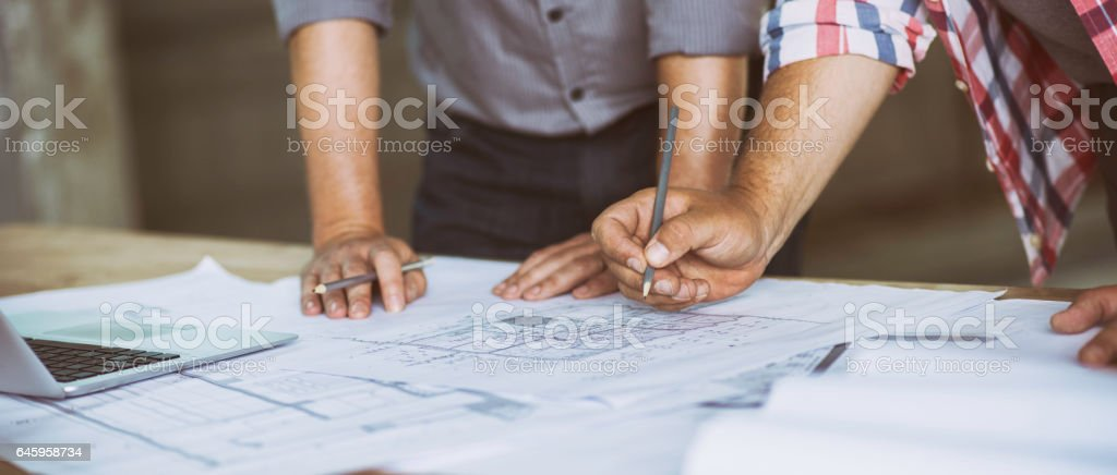 Close up of two people reviewing building blueprints stock photo