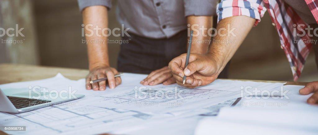 Närbild på två personer granskar byggnad-ritningar bildbanksfoto