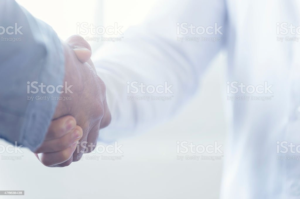 Close up of two people shaking hands. Both people in handshake are...