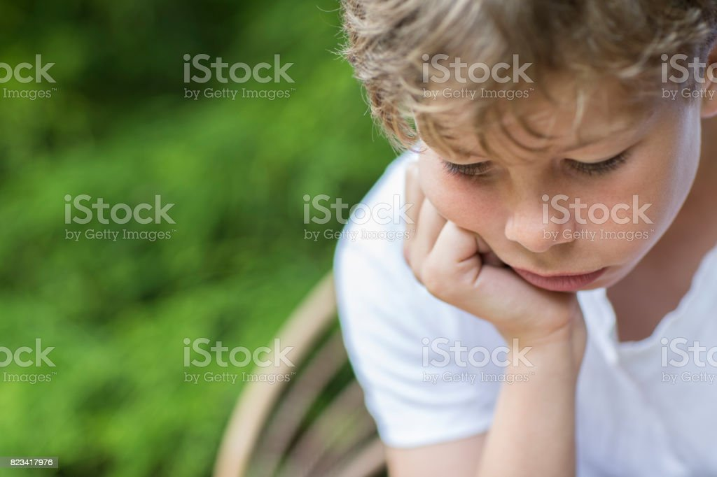 Close Up Of Unhappy Boy Sitting In Chair Outdoors stock photo