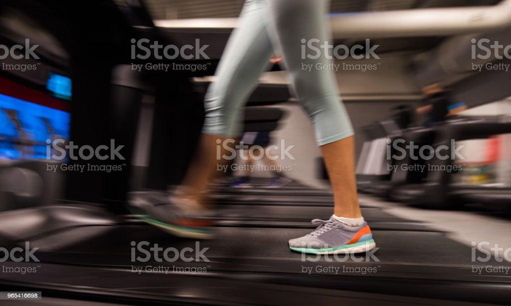 Close up of unknown female running on the treadmill. zbiór zdjęć royalty-free