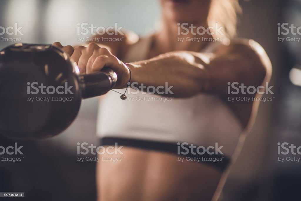 Close up of unrecognizable athlete exercising with kettle bell. stock photo