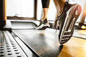 Close up of sole of sneakers of unrecognizable athlete jogging on a treadmill.