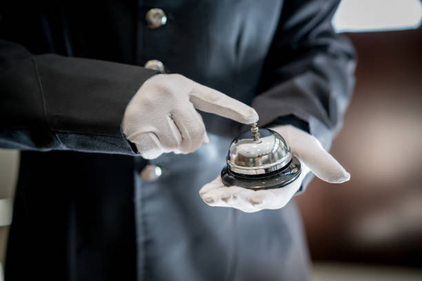 Close up of unrecognizable bell boy at a hotel ringing the bell Close up of unrecognizable bell boy at a hotel ringing the bell using white gloves concierge stock pictures, royalty-free photos & images