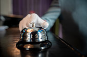Close up of unrecognizable bellhop ringing a bell on hotel check in counter - Hotel occupation concepts