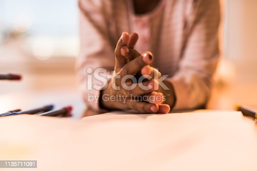 Close p of unrecognizable African American child holding her hands clasped. Copy space.