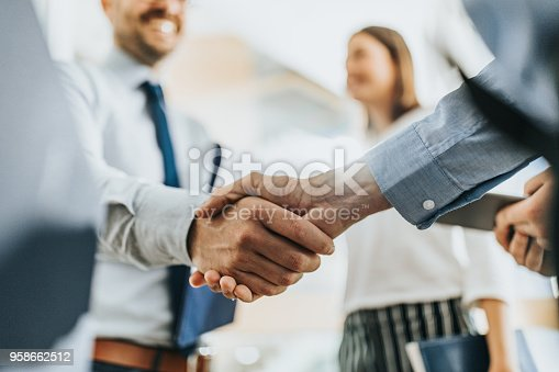 Close up of unrecognizable businessmen shaking hands in the office.