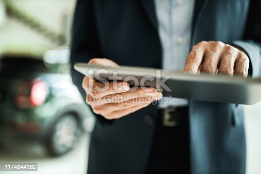 Close up of unrecognizable salesperson using touchpad in a car showroom.
