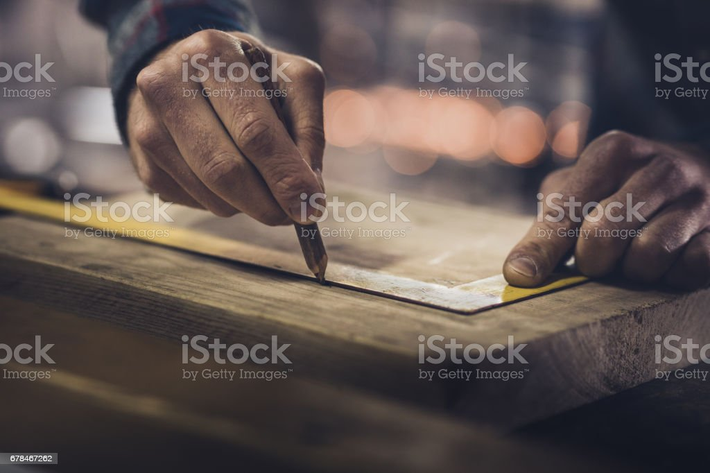 Close up of unrecognizable carpenter drawing measurements on a wood. stock photo