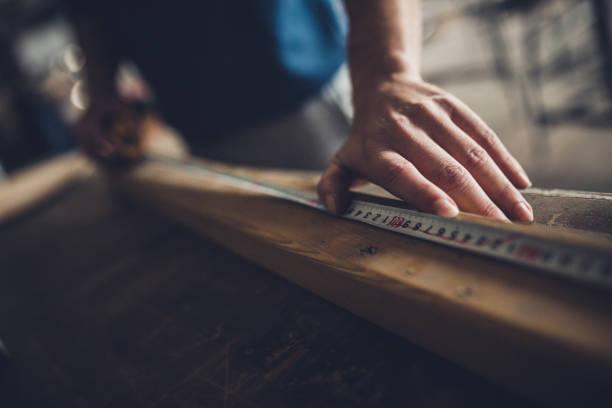 close up of unrecognizable carpenter marking measurements on a piece of wood. - przyrząd pomiarowy narzędzie do pracy zdjęcia i obrazy z banku zdjęć