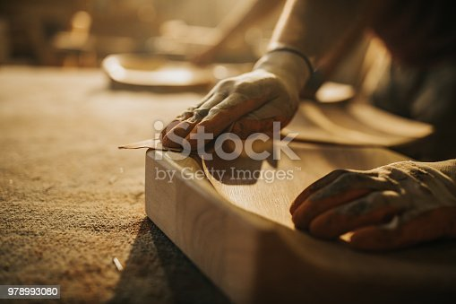 Close up of unrecognizable manual worker using sand paper while working on a wood.