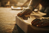 Close up of unrecognizable carpenter restoring a wood with sand paper.