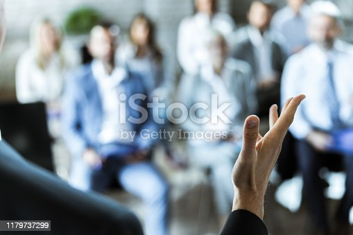 Close up of unrecognizable businessman giving a speech to his colleagues in a board room.