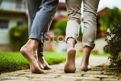 Close up of unrecognizable mature couple walking barefoot in the backyard.