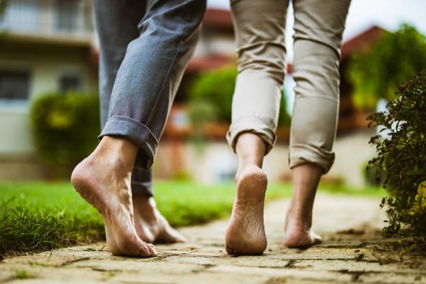 close up of unrecognizable couple walking barefoot in the backyard. - scalzo foto e immagini stock