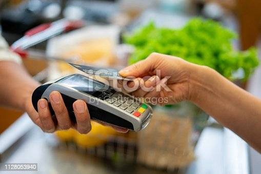 Close up of unrecognizable customer doing a contactless payment at the supermarket **DESIGN ON CREDI CARD WAS MADE FROM SCRATCH BY US**