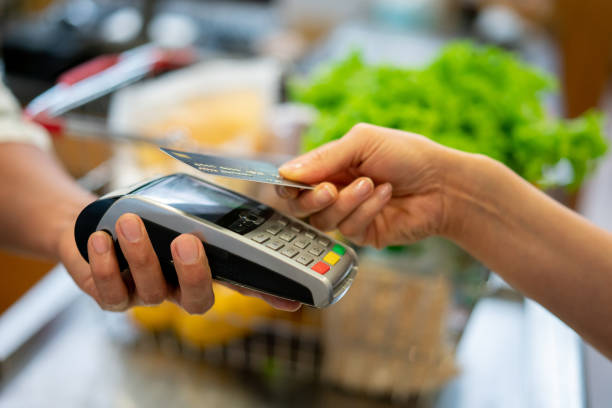 close up of unrecognizable customer doing a contactless payment at the supermarket - credit card imagens e fotografias de stock