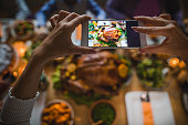 Close up of unrecognizable female person photographing Thanksgiving turkey with cell phone.