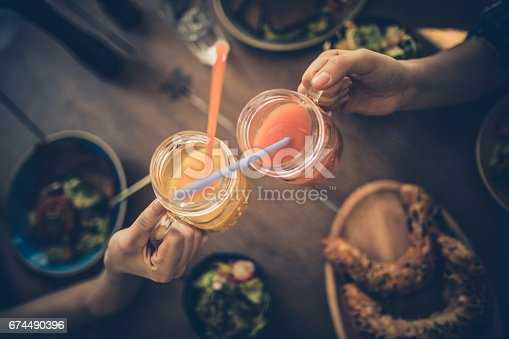 Above view of two unrecognizable women toasting with mocktails in a cafe.