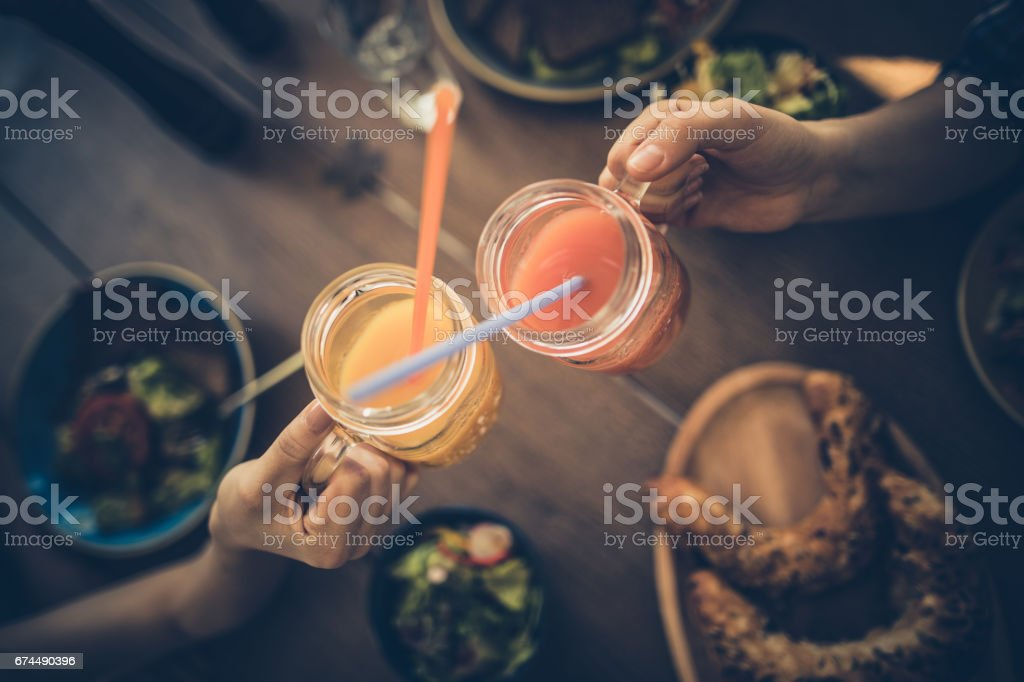 Close up of unrecognizable friends toasting with juices in a restaurant. stock photo