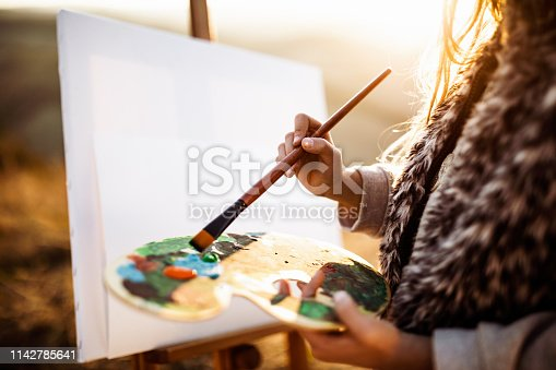 Close up of unrecognizable girl making a painting during autumn day in nature.