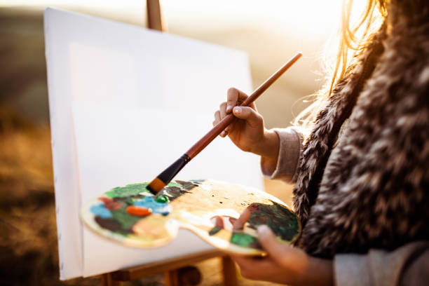 nahaufnahme der unerkennbaren mädchenmalerei in der natur. - naive malerei stock-fotos und bilder
