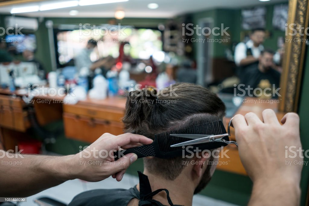 Close up of unrecognizable hair dresser at the barber shop cutting a...