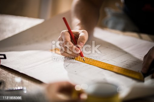 istock Close up of unrecognizable male architect making measurements on housing project. 1131858366
