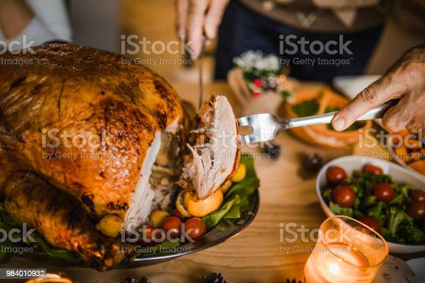 Photo of Close up of unrecognizable man carving roasted Thanksgiving turkey.