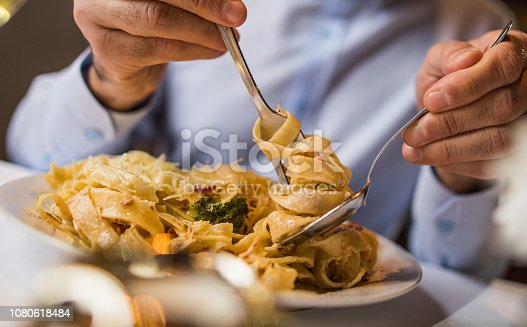 Close up of unrecognizable person eating pasta for dinner.