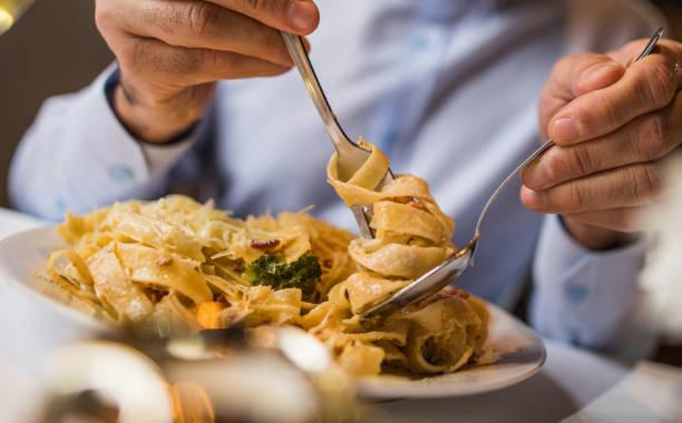 cerca de pasta irreconocible hombre comer para el almuerzo. - comida italiana fotografías e imágenes de stock