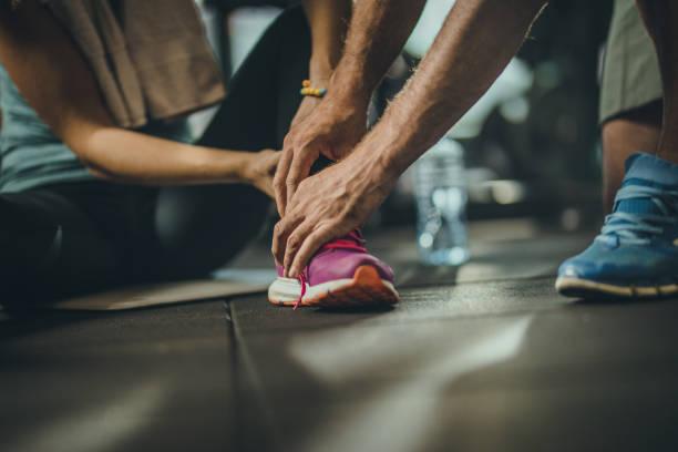 close up of unrecognizable man helping injured sportswoman in a gym. - caviglia foto e immagini stock