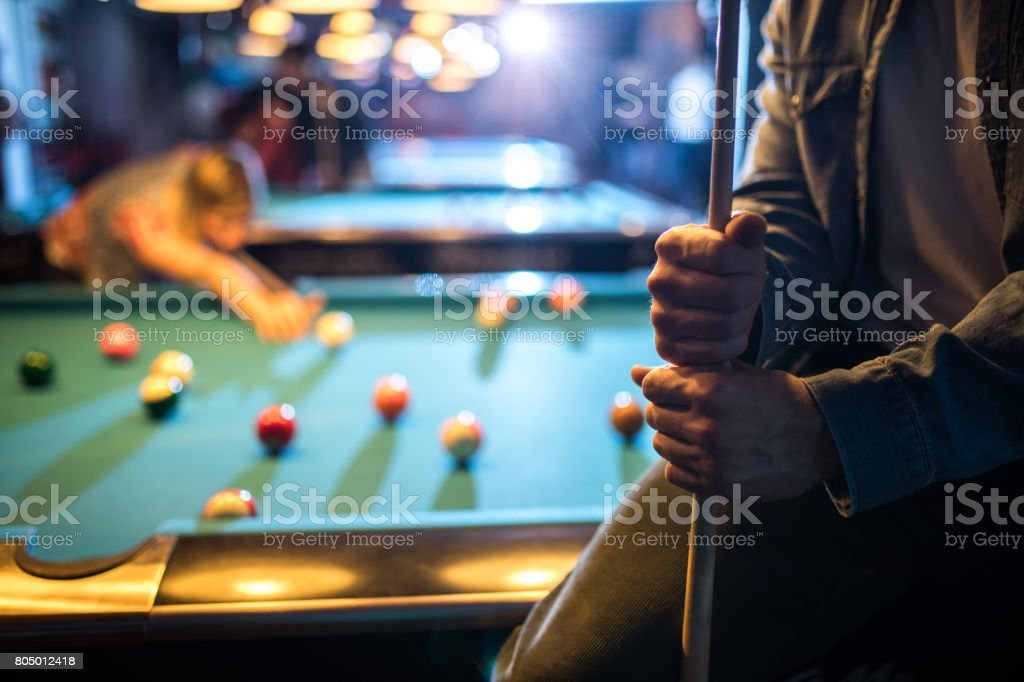 Close up of unrecognizable man holding a pool cue in a pub. stock photo