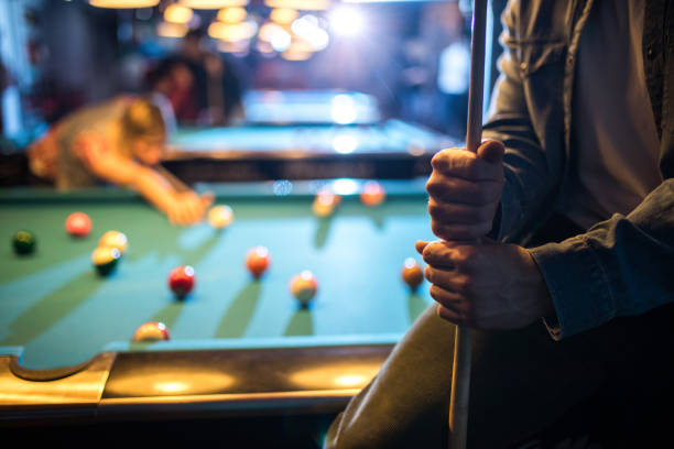 close up of unrecognizable man holding a pool cue in a pub. - pool cue stock photos and pictures