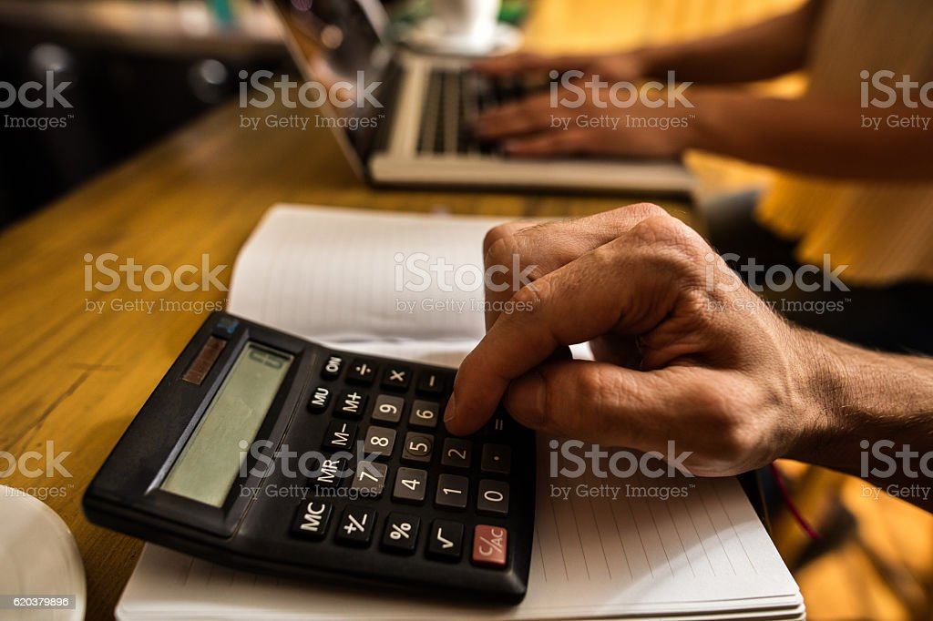 Close up of unrecognizable man using calculator. zbiór zdjęć royalty-free