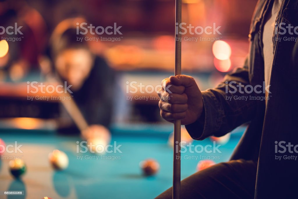 Close up of unrecognizable man with a pool cue in pool hall. stock photo