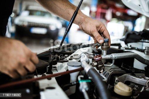 Close up of unrecognizable car mechanic recharging AC in a car.
