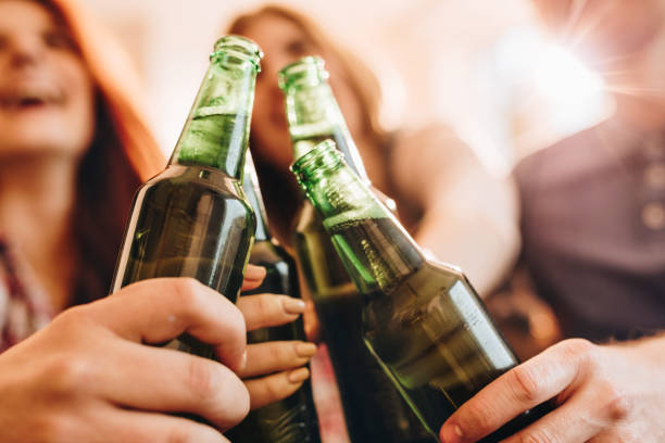 Close up of unrecognizable people toasting with beer. stock photo