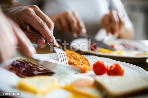 Close up of unrecognizable male person cutting his food during meal at dining table.