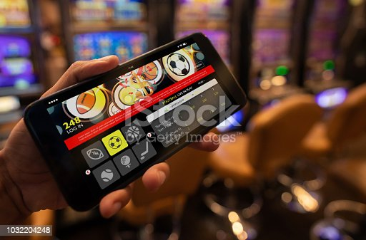 istock Close up of unrecognizable person holding a smartphone with a live football bet application 1032204248