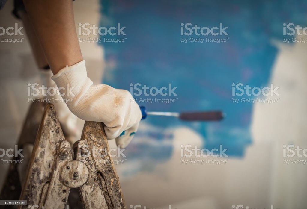 Close up of unrecognizable person on ladders paining walls during...