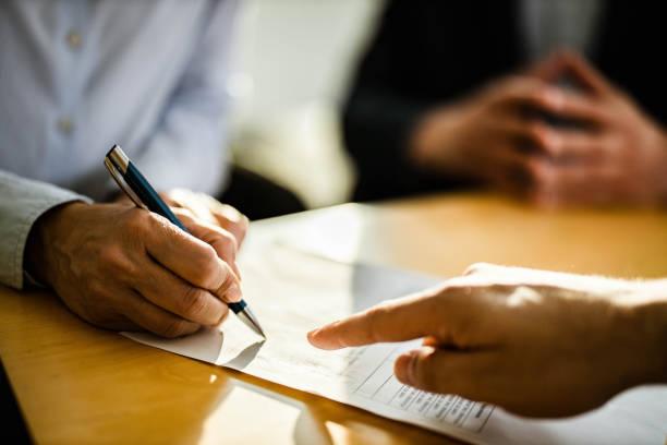 nahaufnahme der nicht wiederzuerkennenden person, die einen vertrag unterzeichnet. - unterschrift stock-fotos und bilder