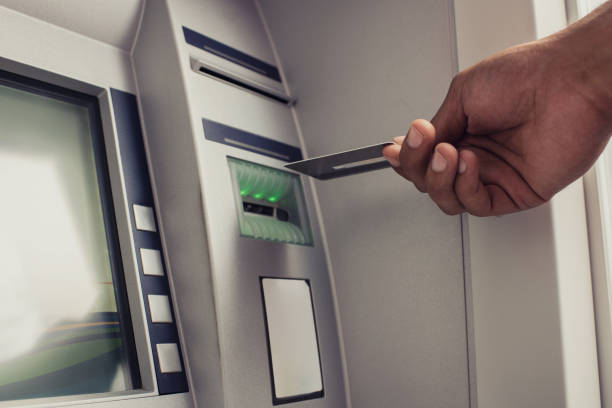 Close up of unrecognizable person with credit card on ATM. stock photo