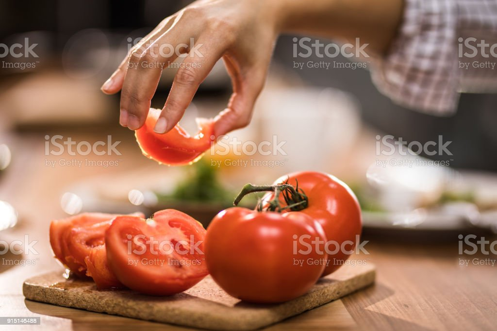 Close up of unrecognizable woman making fresh salad with tomato.