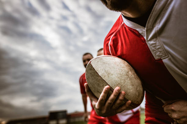 Close up of unrecognizable rugby player with ball. Close up of unrecognizable player carrying rugby ball on a match at playing field. rugby stock pictures, royalty-free photos & images