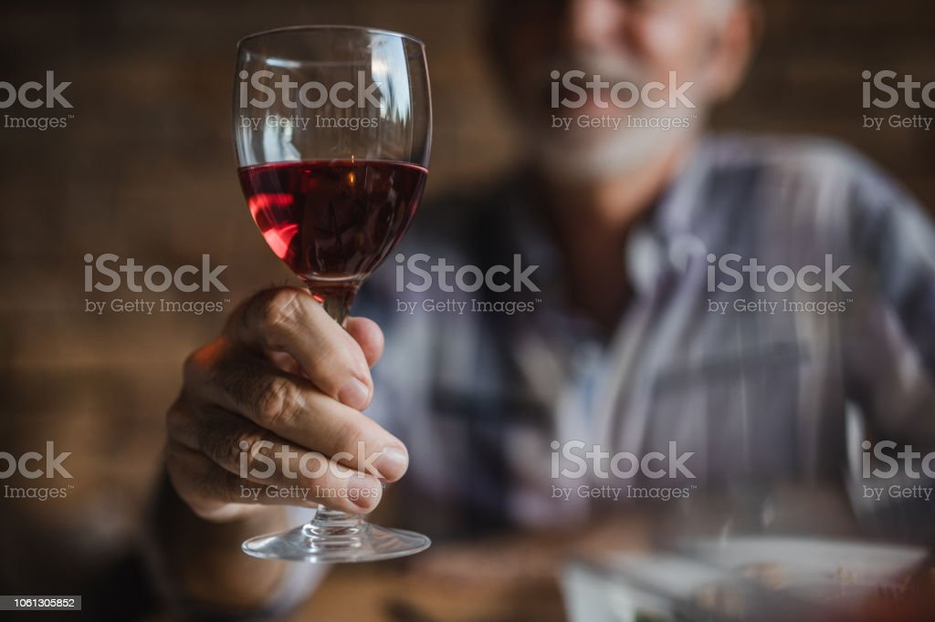 Close up of unrecognizable senior man holding glass of red wine. stock photo