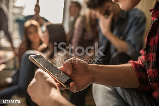 istock Close up of unrecognizable student using cell phone on a break in the classroom. 875179478