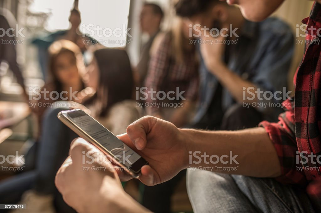 Close up of unrecognizable student using cell phone on a break in the classroom. stock photo